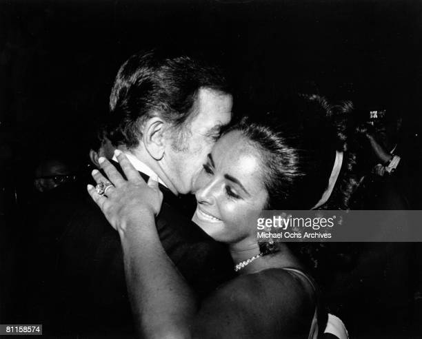 Actress Elizabeth Taylor hugs an unidentified man during the Academy Awards at the Dorothy Chandler Pavilion on April 7, 1970 in Los Angeles,...