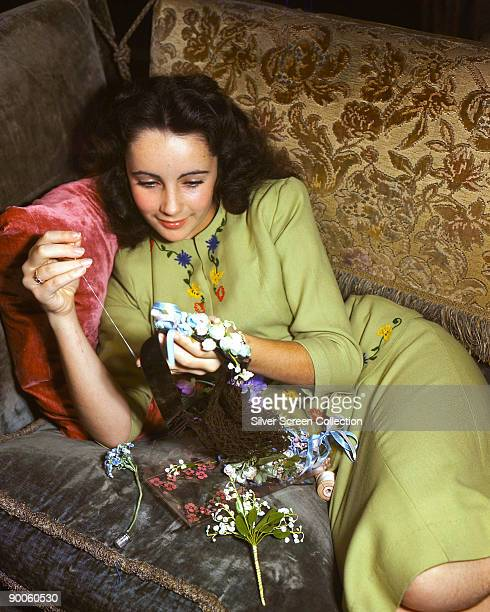 Actress Elizabeth Taylor sewing with artificial flowers, circa 1950.