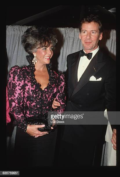 1986 Actress Elizabeth Taylor stands with fashion designer Calvin Klein at an AIDS benefit She wears a lowcut black and pink sequined gown and he...