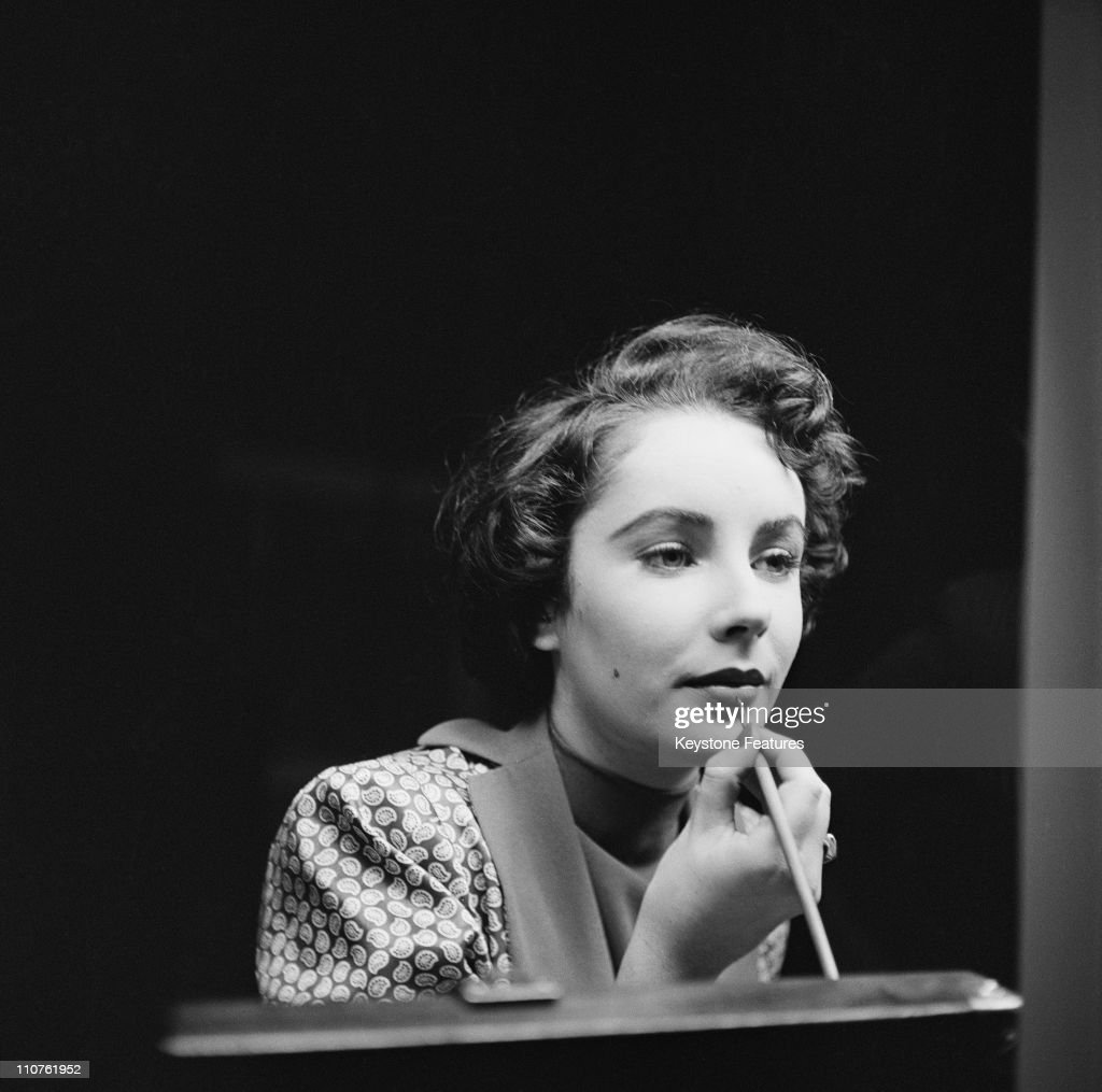 Actress Elizabeth Taylor (1932 - 2011) touches up her lipstick during a stay in London, November 1948.