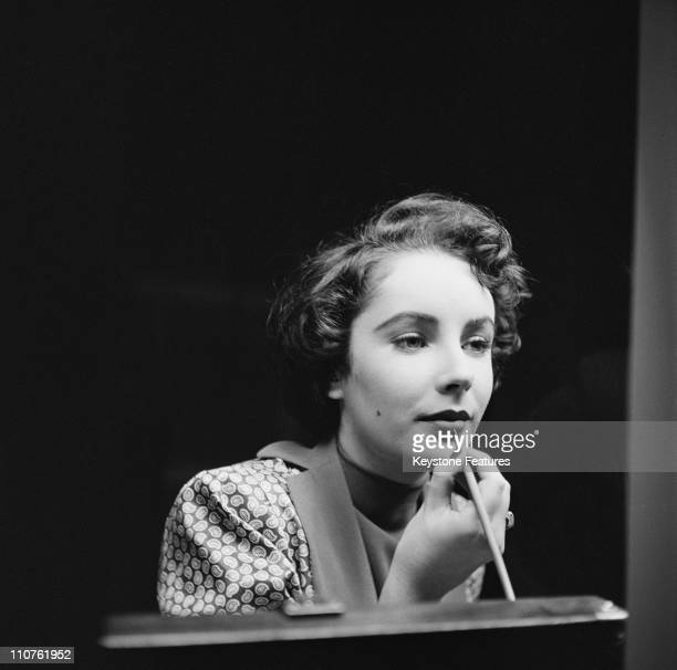 Actress Elizabeth Taylor touches up her lipstick during a stay in London November 1948