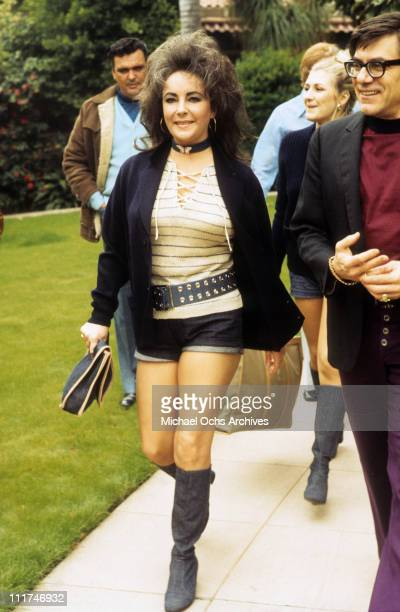 Actress Elizabeth Taylor walking outdoors in short denim shorts and boots March 1971