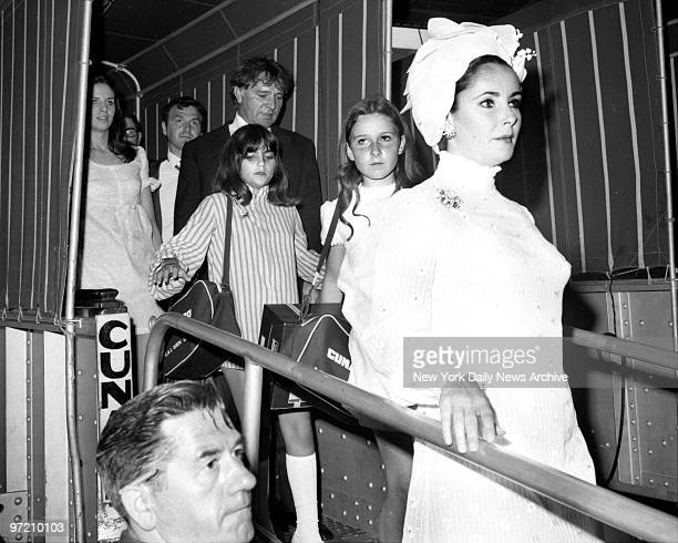 Actress Elizabeth Taylor walks down gangplant of the Queen Elizabeth with husband Richard Burton and her daugther Lisa and his daughter Kate at Pier...