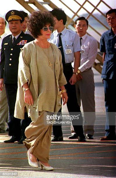 S actress Elizabeth Taylor walks to a van after disembarking from Michael Jackson's private plane which brought them both from Singapore 03 September...