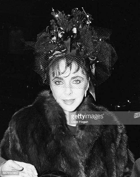 Actress Elizabeth Taylor wearing a fur coat with a ribbon and lace hat as she leaves Annabel's night club in London February 19th 1988