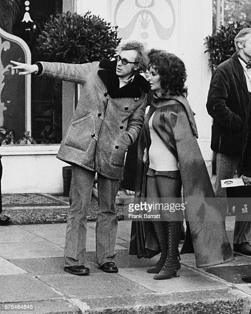 Actress Elizabeth Taylor wearing a long cape over kneehigh boots and hot pants as she is directed by producer Elliott Kastner as they film scenes for...