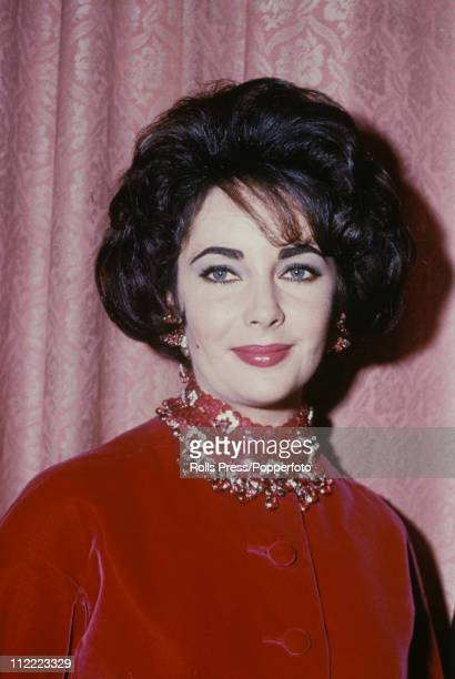 Actress Elizabeth Taylor wearing a red velvet jacket with a jewelled collar and matching earrings circa 1960