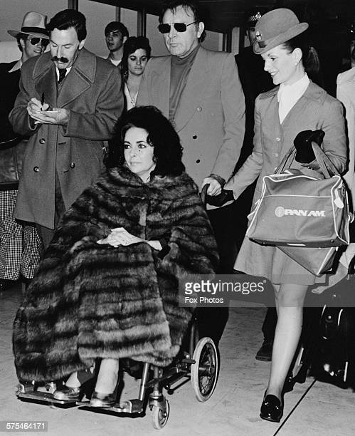 Actress Elizabeth Taylor wears a mink coat as she is pushed through Heathrow Airport in a wheelchair by her husband Richard Burton followed by the...
