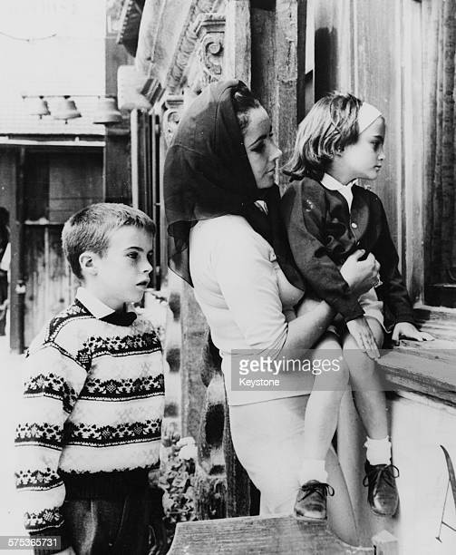 Actress Elizabeth Taylor with her children Chris and Liza window shopping in Gstaad, July 21st 1962.