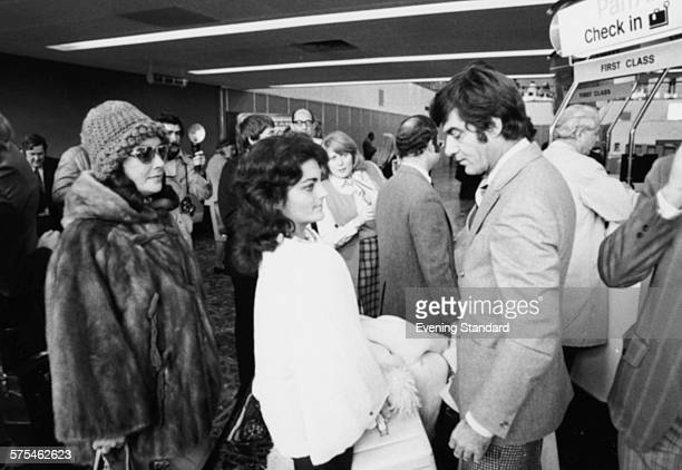 Actress Elizabeth Taylor with her daughter Liza Todd and boyfriend Henry Wynberg surrounded by crowds and press as they arrive at an airport November...