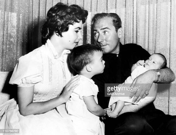 Actress Elizabeth Taylor with second husband Michael Wilding holding son Christopher Wilding while son Michael Wilding looks on 1955