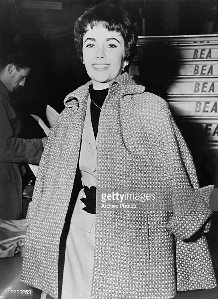 Actress Elizabeth Taylor with short cropped hair and wearing a cape arrives at an airport on a BEA plane 1950s