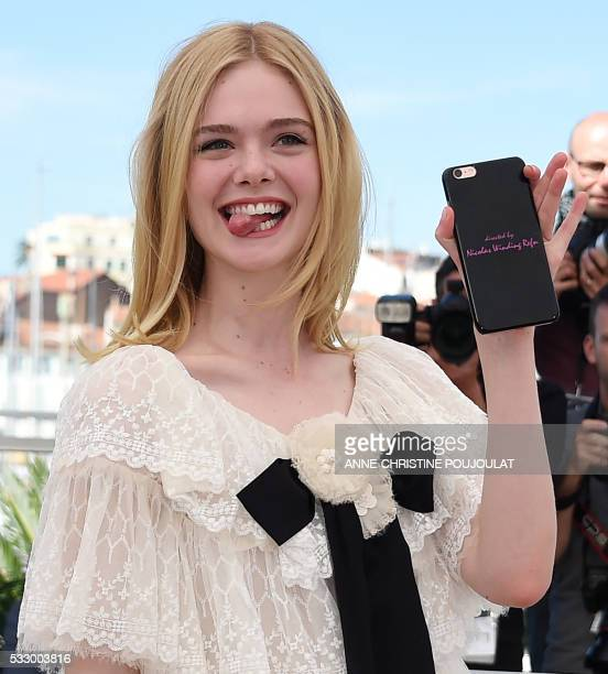US actress Elle Fanning poses with her mobile phone on May 20 2016 during a photocall for the film The Neon Demon at the 69th Cannes Film Festival in...