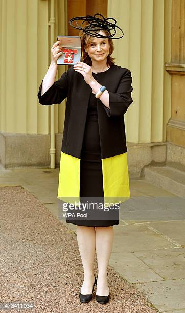 Actress Emily Watson holds her Officer of the Order of the British Empire medal after it was presented to her by the Prince of Wales at the...