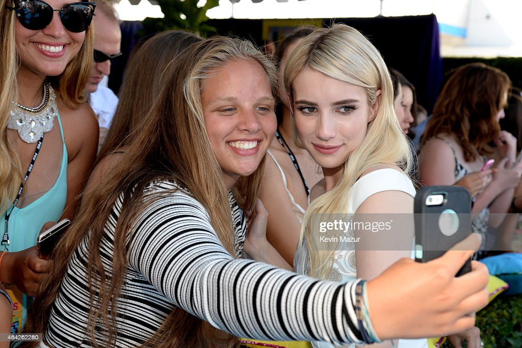 Actress Emma Roberts takes a selfie with a fan during the Teen Choice Awards 2015 at the USC Galen Center on August 16, 2015 in Los Angeles, California.