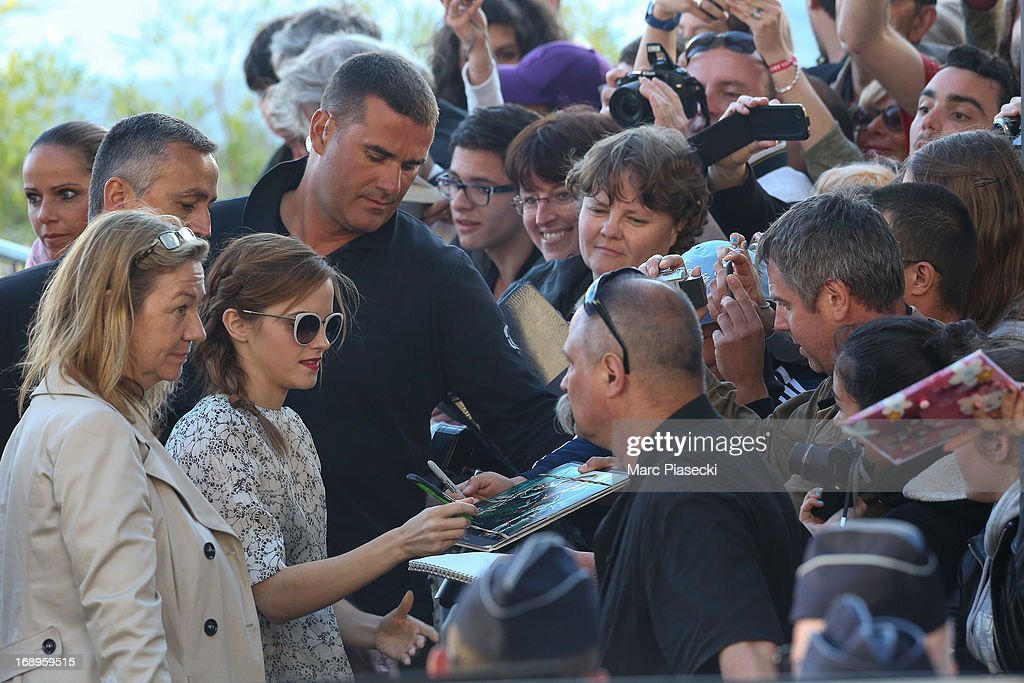 Actress Emma Watson signs autographs as she is seen leaving the 'Le Grand Journal' TV show set during the 66th annual Cannes Film Festival on May 17, 2013 in Cannes, France.