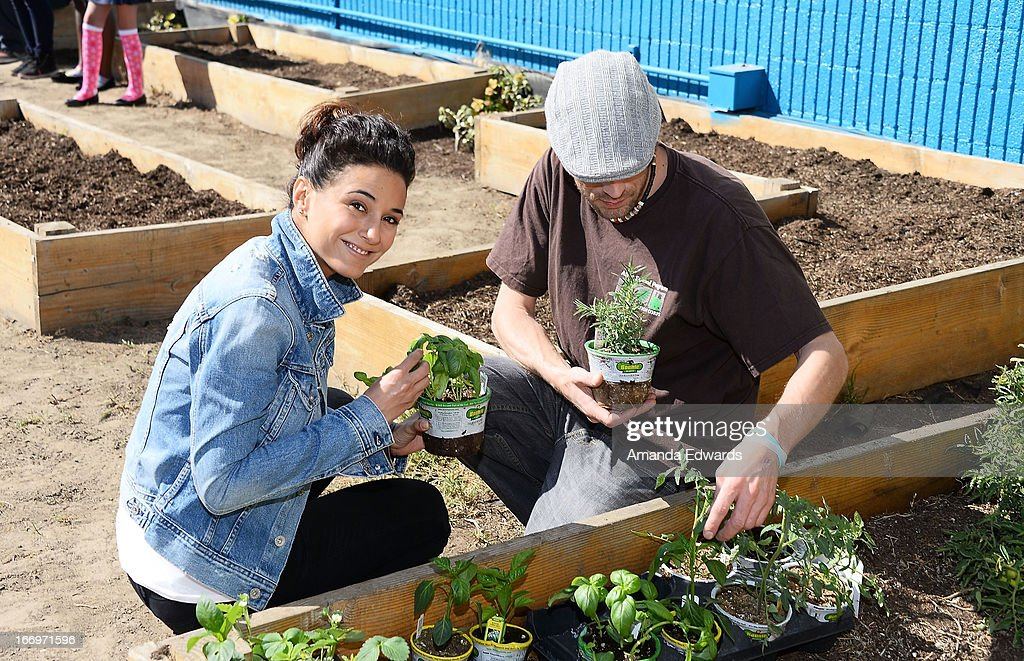 Actress Emmanuelle Chriqui (L) and schoolteacher Joseph Montana celebrate Earth Day with the Environmental Media Association at Cochran Middle School on April 18, 2013 in Los Angeles, California.