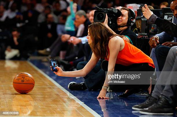 Actress Emmy Rossum takes a photo of the game ball as she attends a game between the New York Knicks and the San Antonio Spurs at Madison Square...