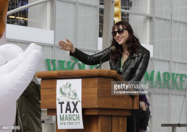 Actress Erin Darke speaking from a podium in front of a Whole Foods Market during a protest demanding that President Donald Trump release his tax...