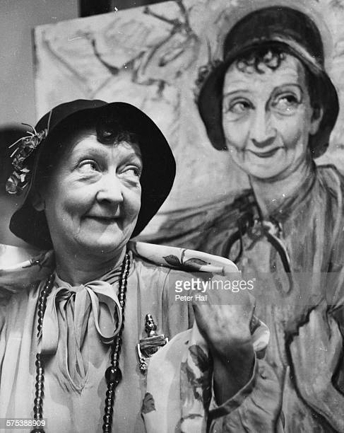 Actress Esma Cannon in costume as Aunt Edie from the play 'Watch it Sailor' beside a portrait of herself by artist Alex Portner at the Aldwych...