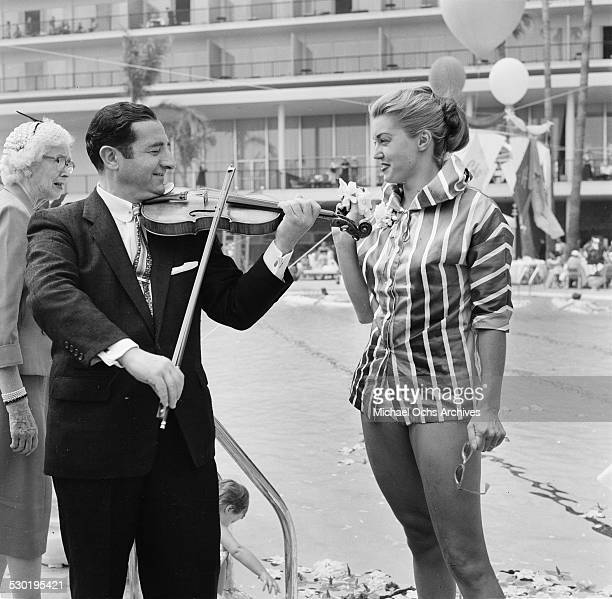 Actress Esther Williams is serenaded pool side at the Hilton Hotelduring the opening day of the Esther Williams Swim School in Los AngelesCA