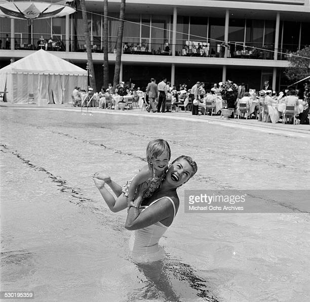 Actress Esther Williams lifts a little girl in the pool during the opening day of the Esther Williams Swim School at the Hilton Hotel in Los AngelesCA