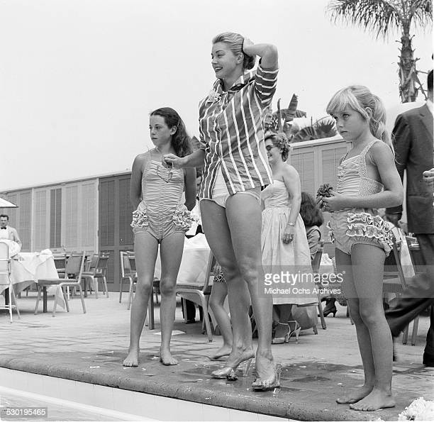 Actress Esther Williams stands pool side with childrenduring the opening day of the Esther Williams Swim School at the Hilton Hotel in Los AngelesCA
