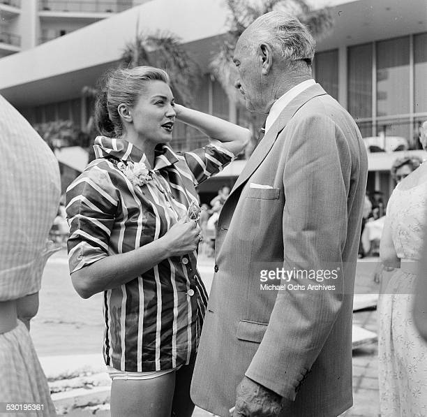 Actress Esther Williams talks with Conrad Hilton at the Hilton Hotel during the opening day of the Esther Williams Swim School in Los AngelesCA