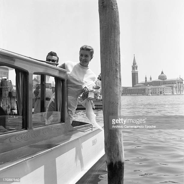 Actress Esther Williams waves from a taxi boat in Venice Italy September 1957