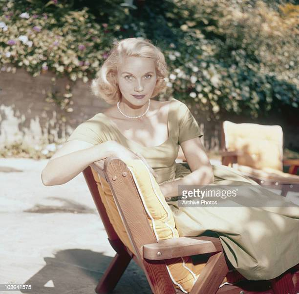 Actress Eva Marie Saint pictured seated on a sun lounger in a garden, USA, circa 1950. Saint is wearing a light green dress and a pearl necklace.
