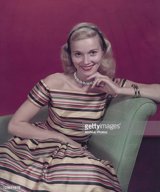 Actress Eva Marie Saint pictured smiling and seated with her left hand supporting her chin USA circa 1950 Saint is wearing a striped multicoloured...