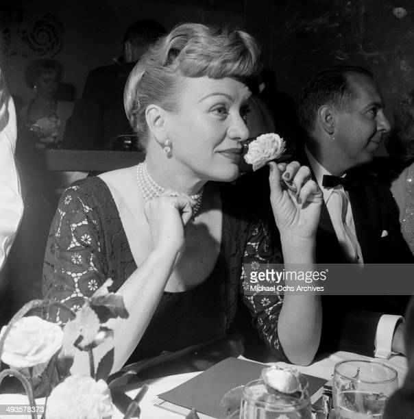 Actress Eve Arden smells a flower at Screen Directors Award dinner in Los Angeles California