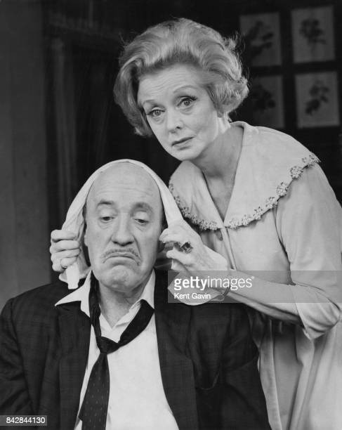 Actress Evelyn Laye administers to Fred Clark's hangover in a rehearsal for the comedy 'Never Too Late' at the Prince of Wales Theatre in London 24th...
