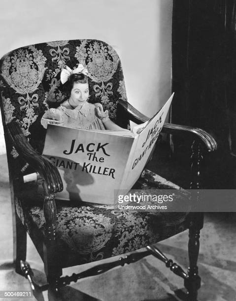 Actress Fanny Brice reading a book in an oversized chair in her role as Baby Snooks on the 'Good News' Radio program Hollywood California 1938