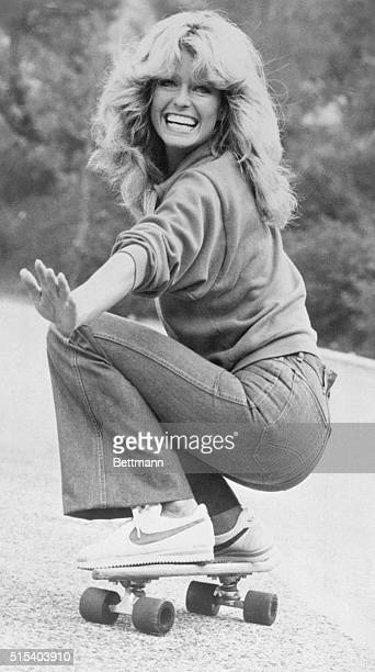 Actress Farrah Fawcett wearing jeans sweatshirt and Nike athletic shoes practices skateboarding for an episode of Charlie's Angels