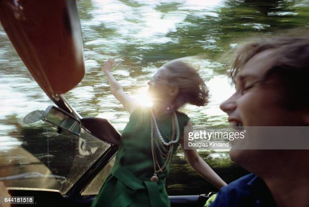 Actress Faye Dunaway hangs out of a convertible as photographer Douglas Kirkland drives with one hand and shoots photos with the other