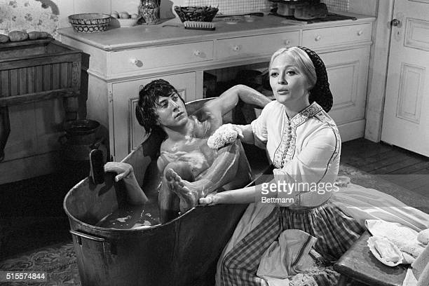 Actress Faye Dunaway looks stern as she handbathes Oscar nominee Dustin Hoffman during the filming of a scene from their first movie together 'Little...