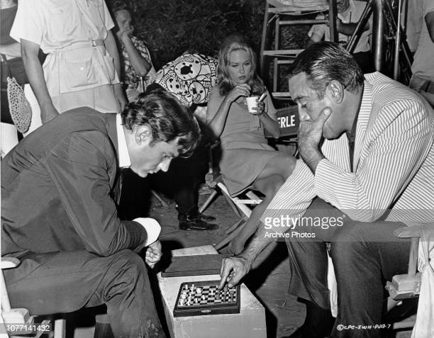 Actress Faye Dunaway watches costars George Maharis and Anthony Quinn playing on a miniature chessboard on the set of the Columbia Pictures film...
