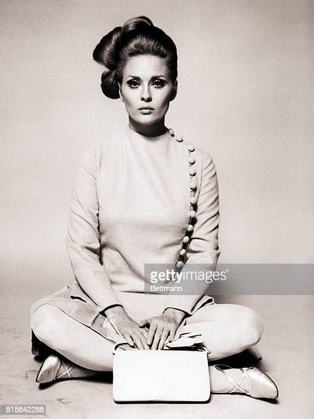 Actress Faye Dunaway wearing a beige broadcloth straitline dress that's buttoned down one side made for the 1968 film The Thomas Crown Affair by...