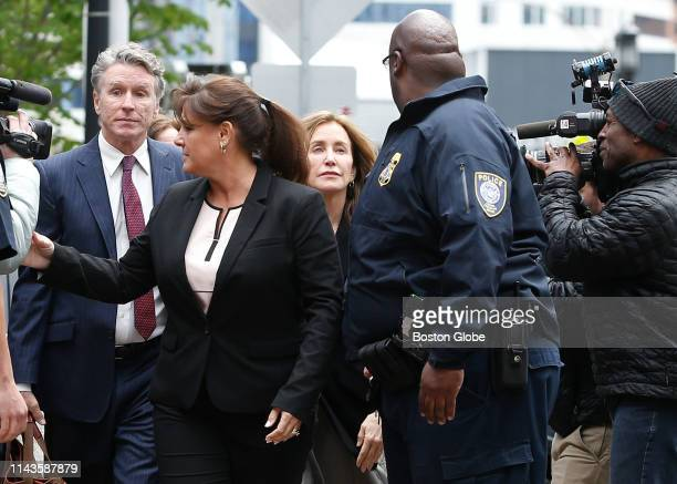 Actress Felicity Huffman center is escorted by a police office as she enters the John Joseph Moakley United States Courthouse with her brother Moore...
