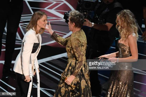 US actress Frances McDormand accepts the Oscar for Best Actress in Three Billboards outside Ebbing Missouri from US actresses Jodie Foster and...