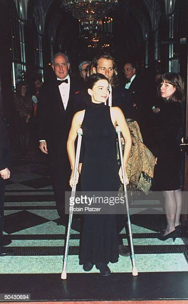 Actress Gabrielle Anwar on aluminum crutches because of a broken foot w unident man at Museum of the Moving Image party in honor of actor Al Pacino...
