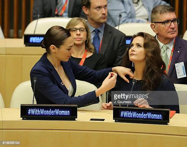 Actress Gal Gadot pins a United Nations Pin to actress Lynda Carter during the Wonder Woman UN Ambassador Ceremony at United Nations on October 21...