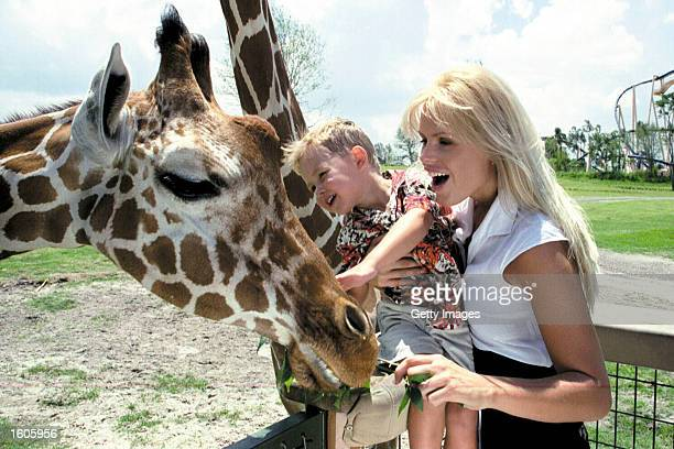 Actress Gena Lee Nolin and her 3yearold son Spencer greet a giraffe at Busch Gardens Tampa Bay''s Serengeti Plain June 30 2000 in Tampa FL