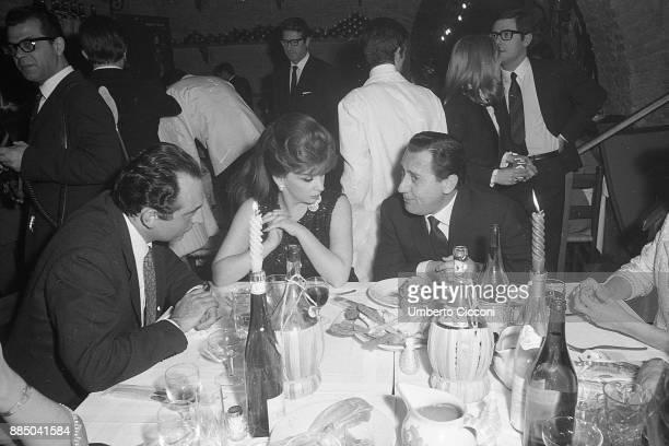 Actress Gina Lollobrigida actor Alberto Sordi and Leone Piccioni at the restaurant with friends Rome 1967