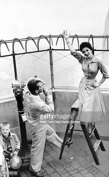 Actress Gina Lollobrigida poses for her husband Dr Milko Skofic on top of the Empire State Building while William J Keary president of the Empire...