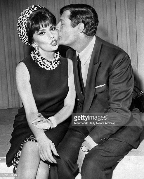 Actress Gina Lollobrigida receives kiss from Marcello Mastroianni at Kennedy Airport
