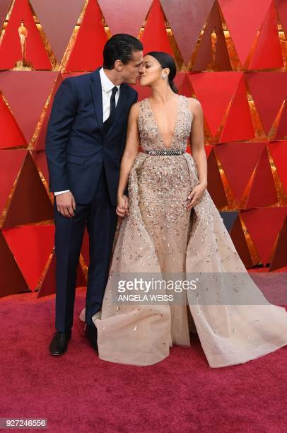 US actress Gina Rodriguez and her partner Joe Locicero kiss as they arrive for the 90th Annual Academy Awards on March 4 in Hollywood California /...