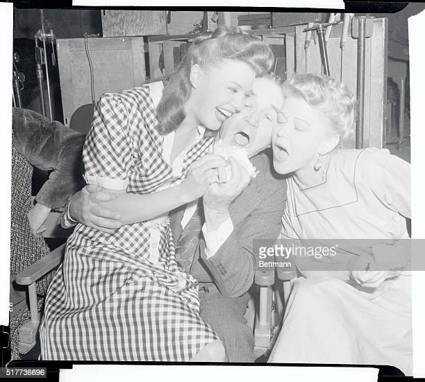 Actress Ginger Rogers her mother and her grandfather concentrate all efforts on one poor defenseless sandwich in recent snacktime maneuvers Ginger...