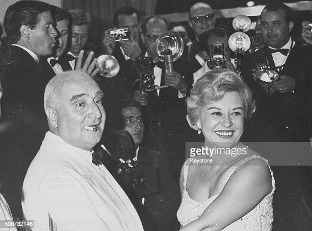Actress Giulietta Masina and film producer Angelo Rizzoli surrounded by press photographers at the Venice Film Festival Italy August 24th 1960